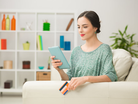 spending money: portrait of young caucasian woman holding digital tablet and credit card, spending money online while relaxing at home Stock Photo