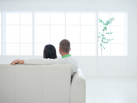 purchased: young caucasian couple sitting on couch in newly purchased apartment Stock Photo