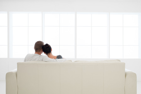 back view of young couple in love relaxing on sofa Standard-Bild