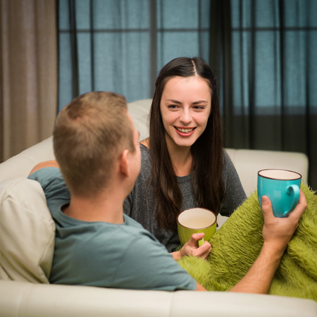 young happy couple on couch drinking tea at home and laughing photo