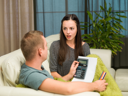 caucasian couple sitting on couch at home calculating payments photo