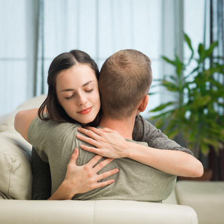 eyesclosed: portrait of young caucasian couple relaxing on sofa at home, embracing each other