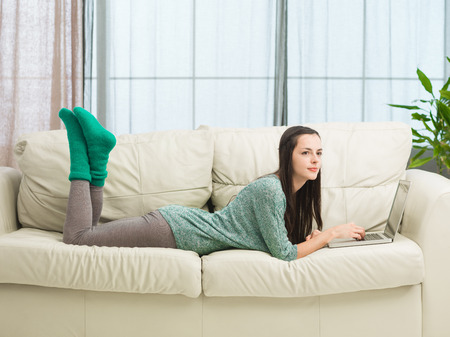 young beautiful caucasian woman lounging in living room on couch with laptop photo