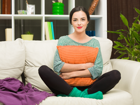 yoga pillows: front view of beautiful young woman sitting on cosy sofa at home, hugging a pillow and smiling