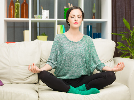 eyesclosed: young caucasian woman doing yoga on sofa at home. lotus pose Stock Photo