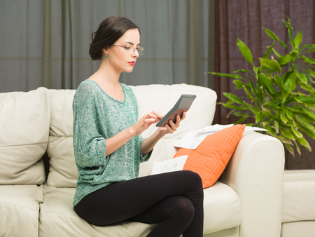 young beautiful caucasian woman sitting on sofa at home, doing her accounts photo