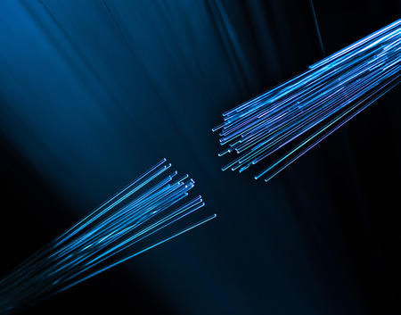 glass fiber: two fiber optic cables connecting on defocused background