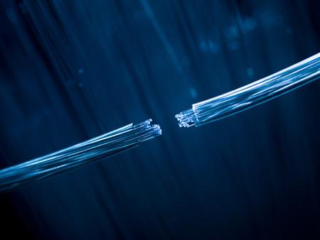 Twee glasvezelkabels die op defocused achtergrond verbinden