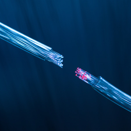 glass fiber: macro of two fiber optic cables connecting on defocused background Stock Photo