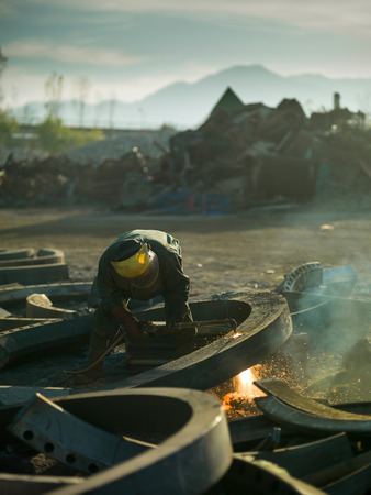 recycling center: male worker wearing protective equipment welding metal in recycling center Stock Photo