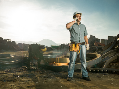 caucasian male engineer standing in recycling center, talking on phone, with man welding metal in background photo