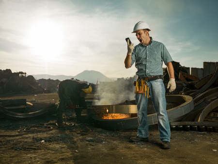 junkyard: caucasian male engineer standing in recycling center, yelling at phone, with man welding metal in background