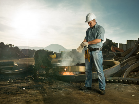 recycling center: caucasian male engineer standing in recycling center,putting gloves, with man welding metal in background. copy space available Stock Photo