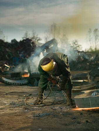 worker with protective equipment welding metal photo