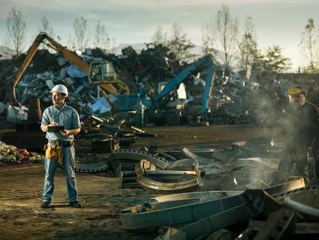 白人のエンジニア、スクラップ金属のリサイクル サイトに立って検査作業