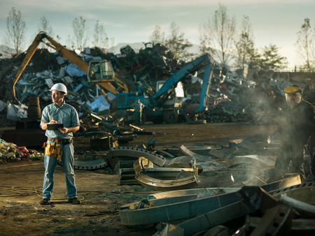 caucasian engineer standing at scrap metal recycling site, inspecting work