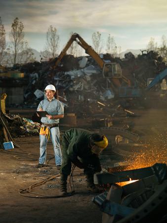 metallschrott: kaukasisch-Ingenieur Stehen bei Schrott-Recycling vor Ort, die Kontrolle der Arbeit