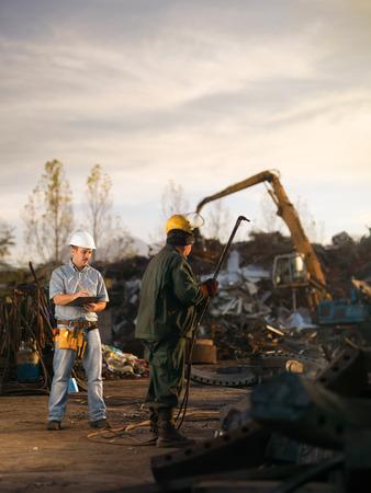grabber: caucasian engineer standing at scrap metal recycling site, inspecting work
