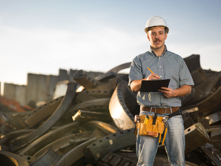 portrait of happy caucasian worker standing in metal landfill outdoors, writing photo