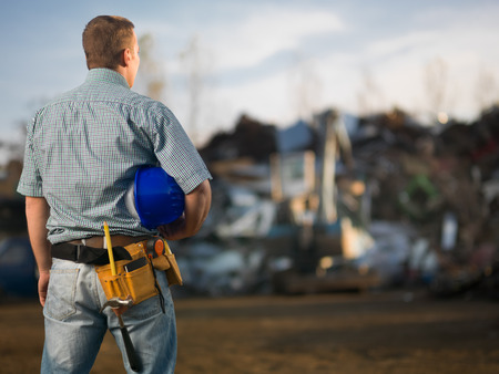 recycling center: back view of engineer holding hardhat, standing in scrap metal recycling center. selective focus
