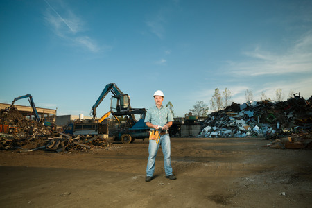 landfill site: portrait of happy caucasian worker standing in metal landfill outdoors
