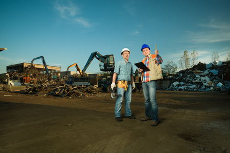 recycling center: two caucasian engineers standing in recycling center outdoors, talking