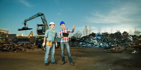 recycling center: two caucasian engineers standing in recycling center outdoors, talking and pointing at something Stock Photo