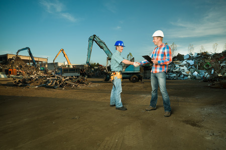 two caucasian engineers standing in recycling center outdoors shaking hands Standard-Bild
