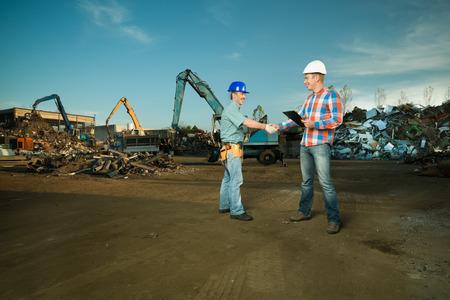 twee blanke ingenieurs staan in recyclingcentrum buitenshuis handen schudden