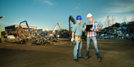 two caucasian engineers standing in recycling center outdoors, talking about a plan photo