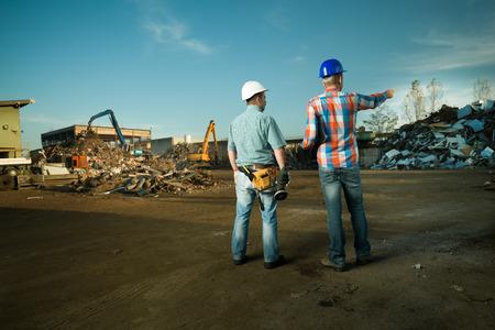 リサイクルで立っている 2 人の白人エンジニア センター屋外で金属スクラップの山を指して