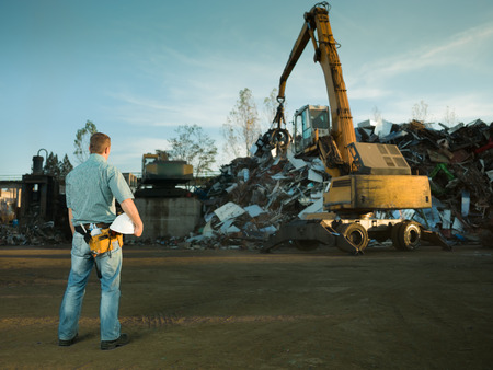 metal recycling: worker standing in recycling landfill looking at scrap metal stack Stock Photo