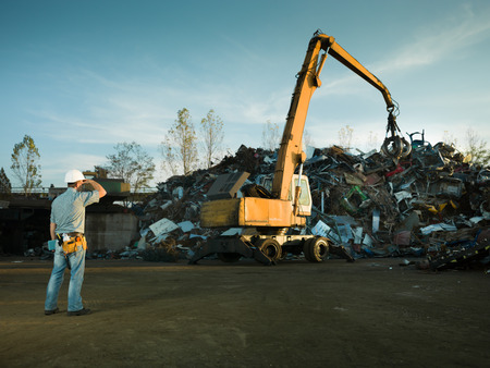 grabber: worker standing in recycling landfill looking at scrap metal stack Stock Photo