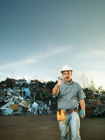 junkyard: portrait of young caucasian engineer holding thumb up in scrap metal landfill outdoors. copy space available