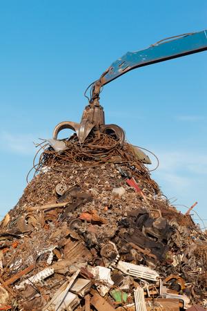 grabber: crane holding rusty metal in recycling junkyard Stock Photo