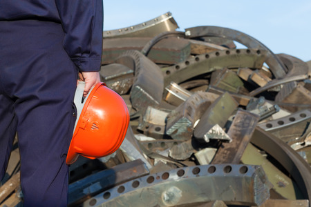 disposed: closeup of worker holding helmet standing facing pile of disposed metal in junkyard