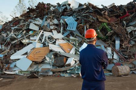 werknemer staan in de voorkant van de stapel geplaatste objecten in recycling centrum Stockfoto
