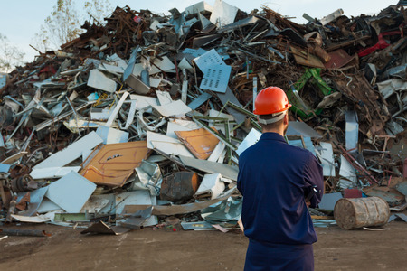 worker standing in front of pile of disposed objects in recycling center