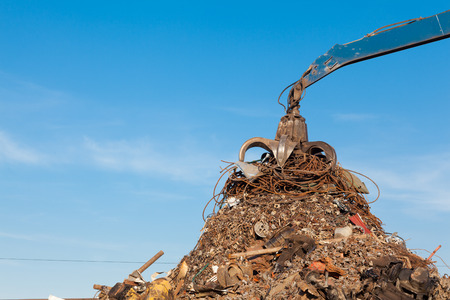 discarded metal: crane holding rusty metal in recycling junkyard Stock Photo