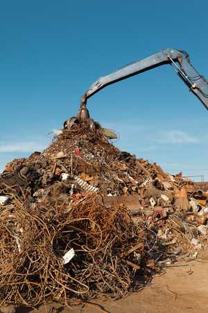 junkyard: crane holding rusty metal in recycling junkyard Stock Photo