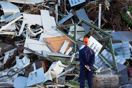 junkyard: worker standing in front of pile of disposed metal in junkyard, wearing protective equipment