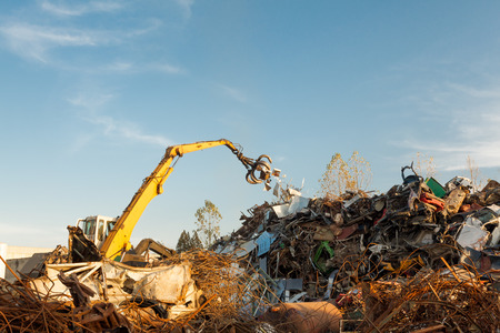 metal recycling: crane picking up scrap metal in recycling site outdoors