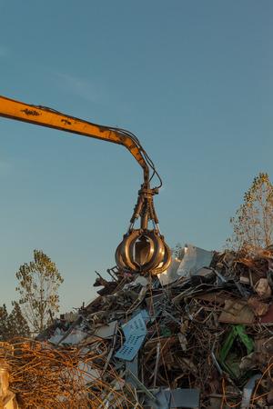 grabber: crane holding scrap metal on top of pile of junk Stock Photo