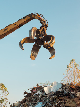 discarded metal: crane with open claw on top of pile with scrap metal