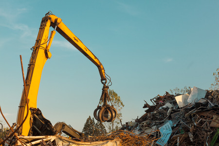 metal recycling: crane claw on top of pile with scrap metal in recycling center