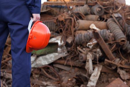 disposed: back view worker holding helmet standing facing pile of disposed metal in junkyard