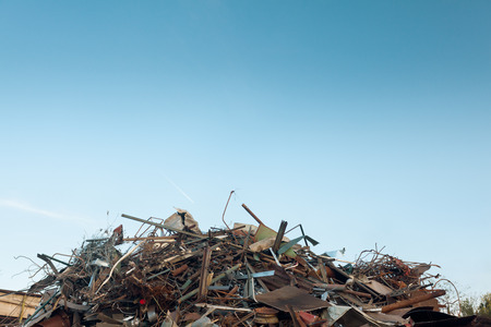recycling center: pile of scrap metal at recycling center, with clear blue sky