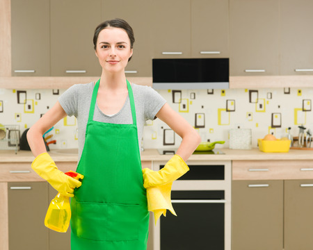 cleaning kitchen: young caucasian woman with cleaning workwear and supplies standing in kitchen, getting ready for spring cleaning