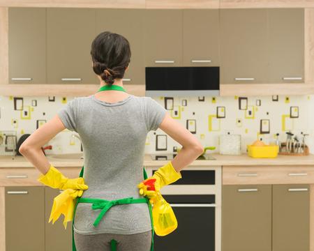 casalinga: vista posteriore della giovane casalinga si prepara per la pulizia della cucina