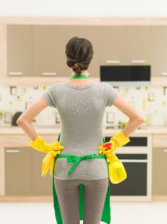 housecleaning: back view of young woman getting ready for kitchen cleaning